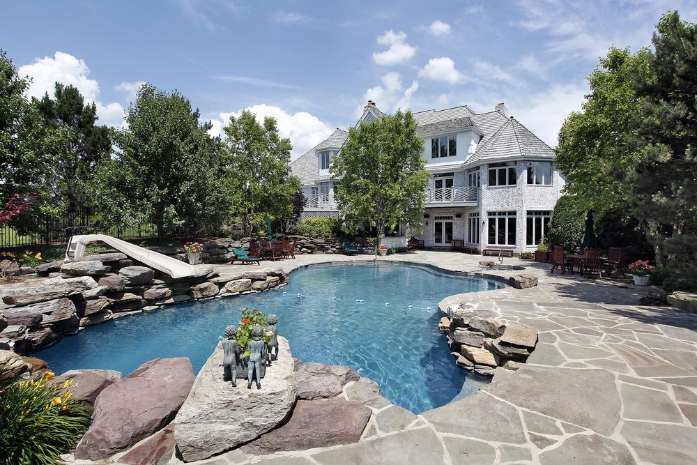 piscine paysagée en pierre à l'arrière d'une maison