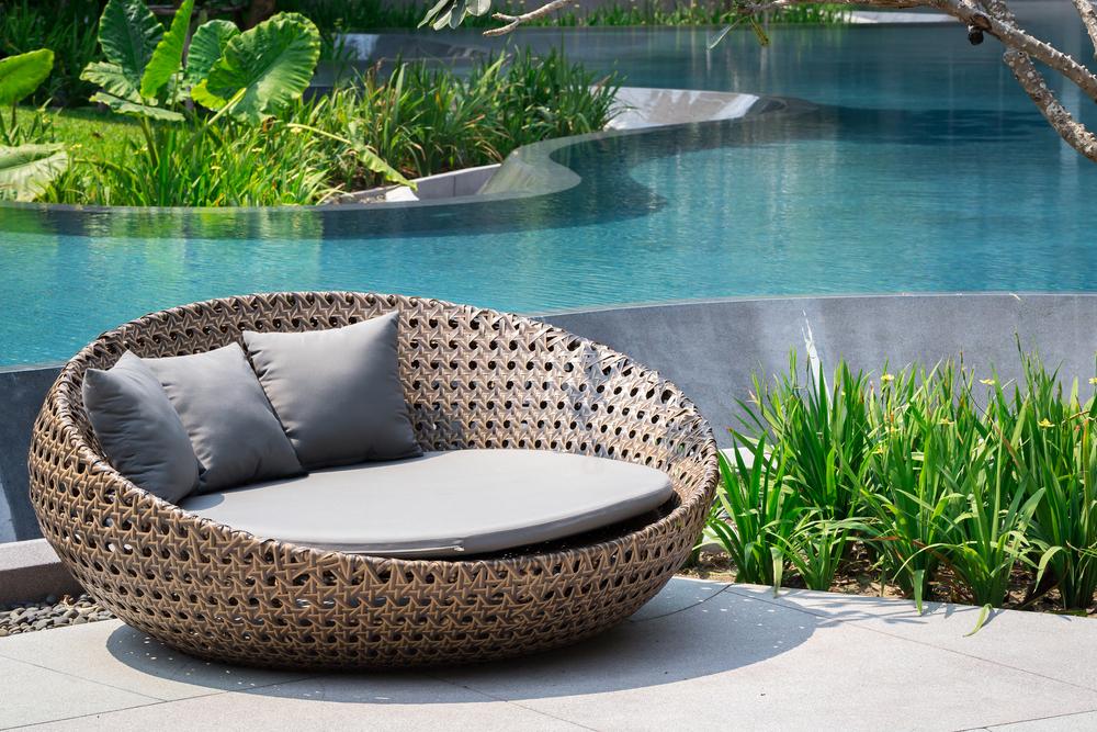 feauteuil en résine tressée au bord d'une piscine